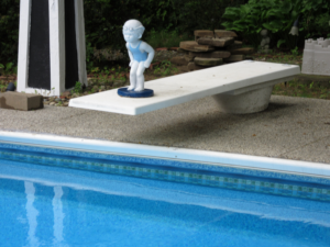 "alt=""statue on diving board at end of in ground pool"""