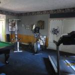 "alt=""view to show corner of pool table bow flex elliptical and treadmill in rec room"""