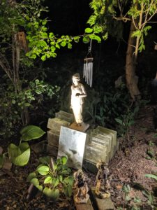 "alt=""welcoming statue to night visions in hallauer house garden"""